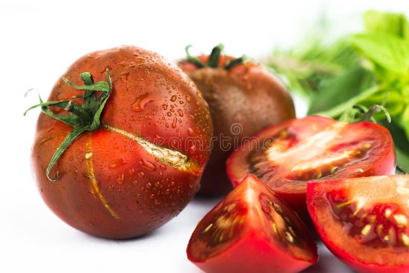 Mörker - röd tomat, helt och halverat på vit royaltyfri bild