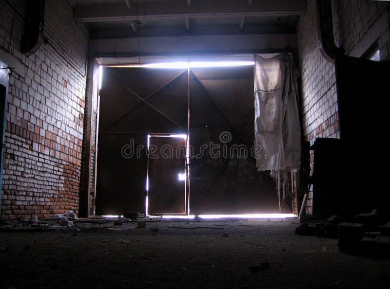 Mörker stängde dörren till garaget, ett tekniskt rum med översikten av utgångsljuset som kommer i sprickorna arkivfoto
