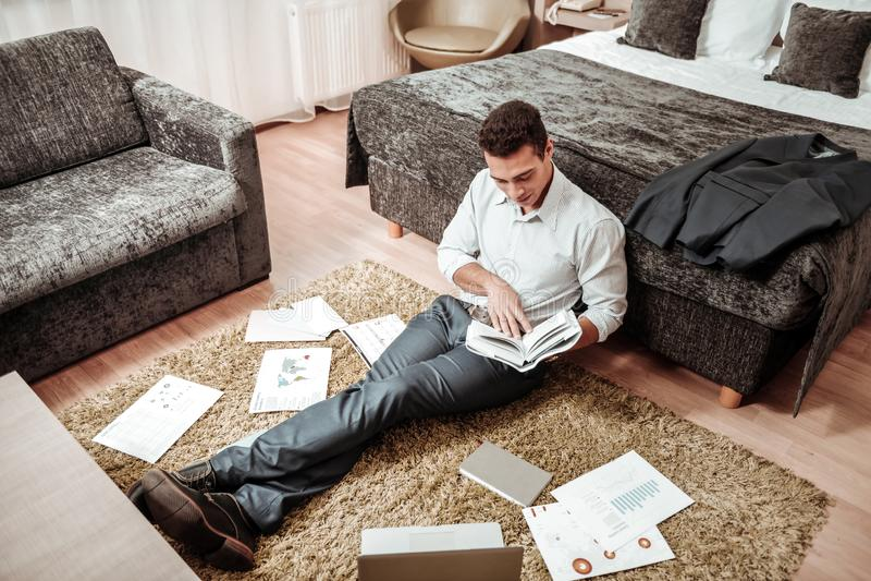 Mörkhårig man som sitter på golvet av hotellrum och hårt arbetar arkivbild