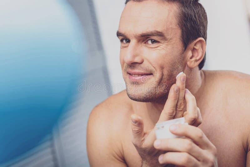 Mörkhårig man som tar omsorg av hans hud arkivfoto