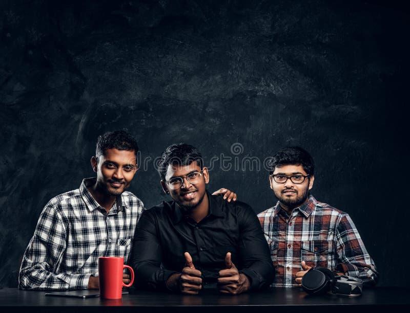 Mörkhyad grabb som tre poserar upp sammanträde på tummarna för lyfta för tabell royaltyfri fotografi