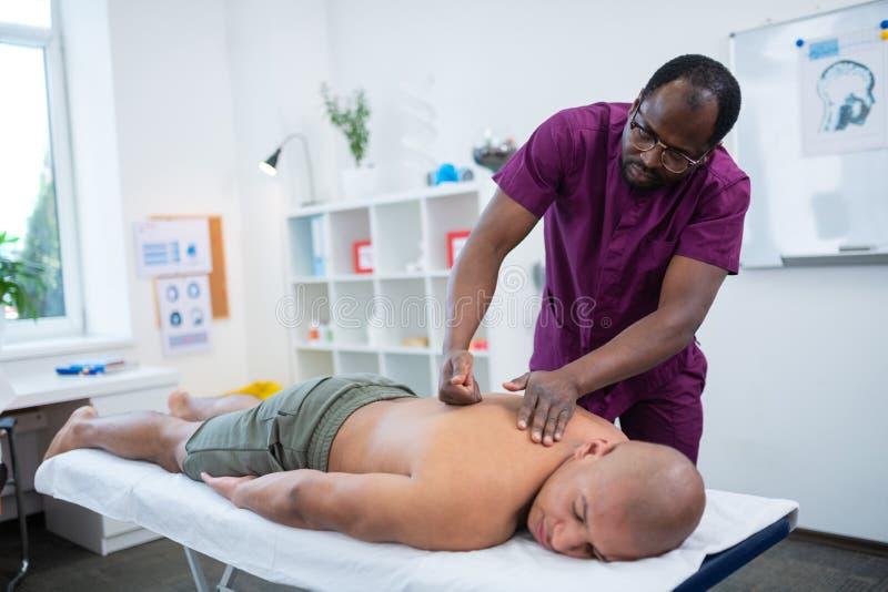 Mörkhyad massageterapeut som använder nävar, medan göra massage royaltyfri bild