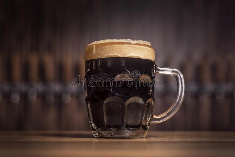 Mörkt öl i ett stort öl rånar ställningar på stången royaltyfri fotografi