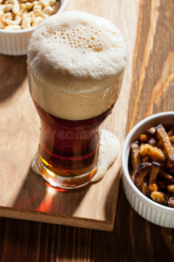Mörkt öl med mellanmål royaltyfri bild
