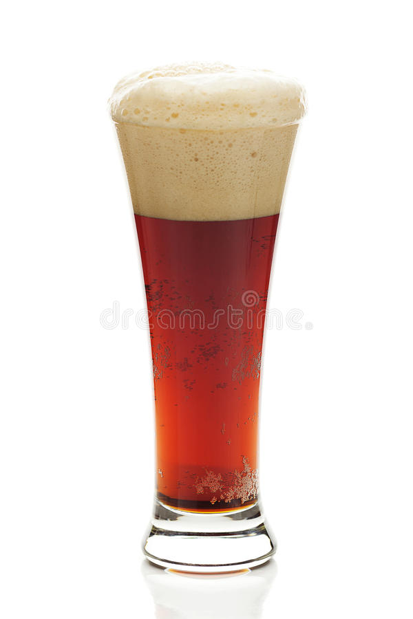 Mörkt öl med skumet i ett högväxt exponeringsglas arkivbild