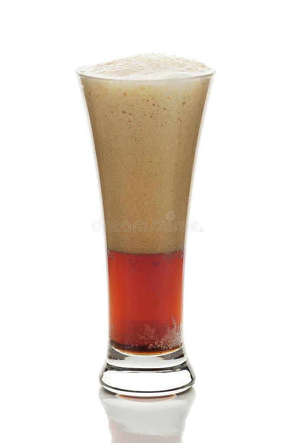 Mörkt öl med skumet i ett högväxt exponeringsglas royaltyfri foto