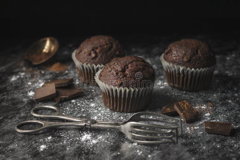 Mörkt atmosfäriskt slut upp av chokladmuffin på lantligt socker c royaltyfria foton