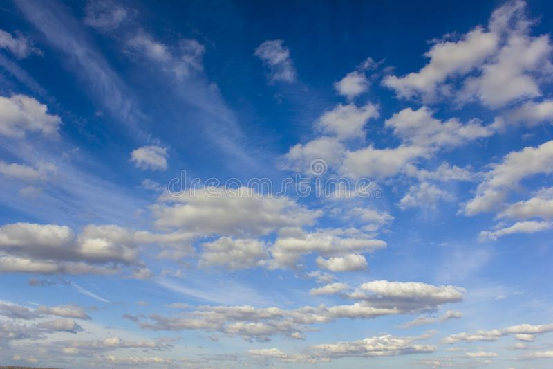 Mörkt - blå himmel med massor av vit försilvrar moln fotografering för bildbyråer