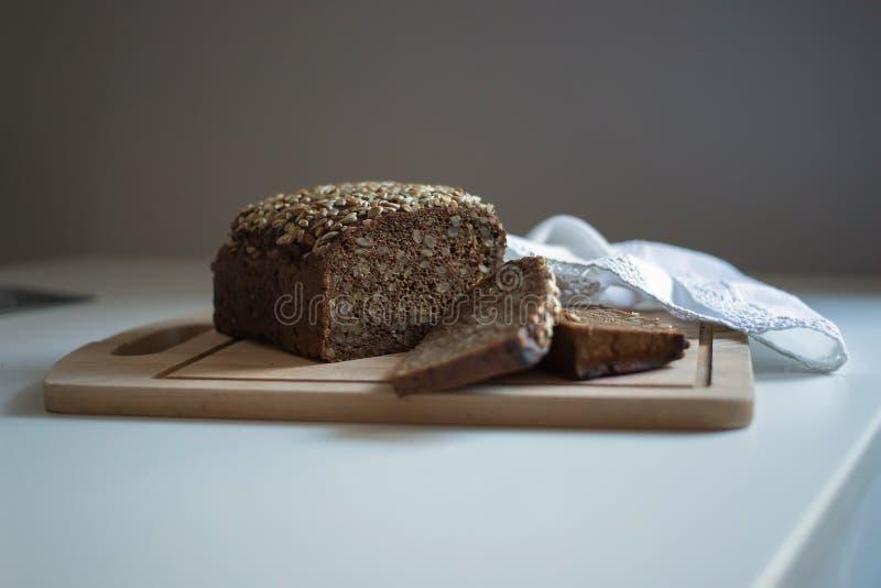 Mörkt bröd med frö på den vita tabellen royaltyfria bilder