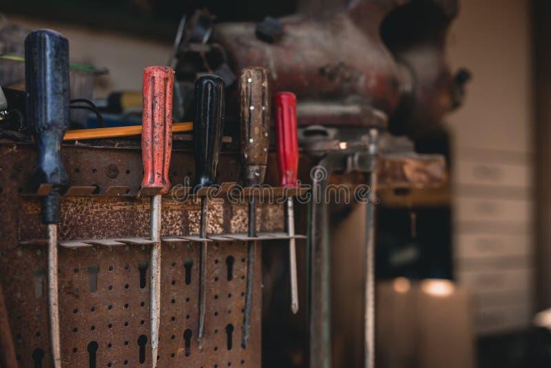 Mörkt foto av skruvchaufförer som hänger på hjälpmedelpanelen i gammalt skjul på solnedgång Nära övre foto av färgrika  arkivbild