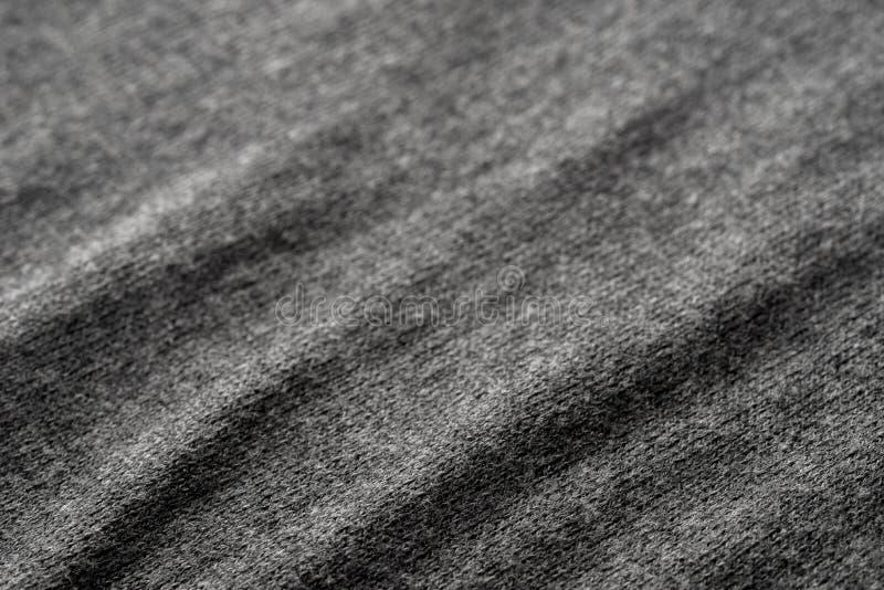 Mörkt - grå ärmlös tröja vikt textiltexturbakgrund arkivbild