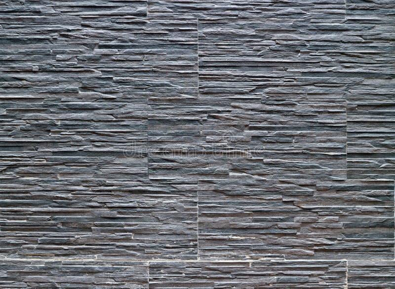 Mörkt - grå claddingvägg som göras av stengodspaneler med steneffekt royaltyfria foton