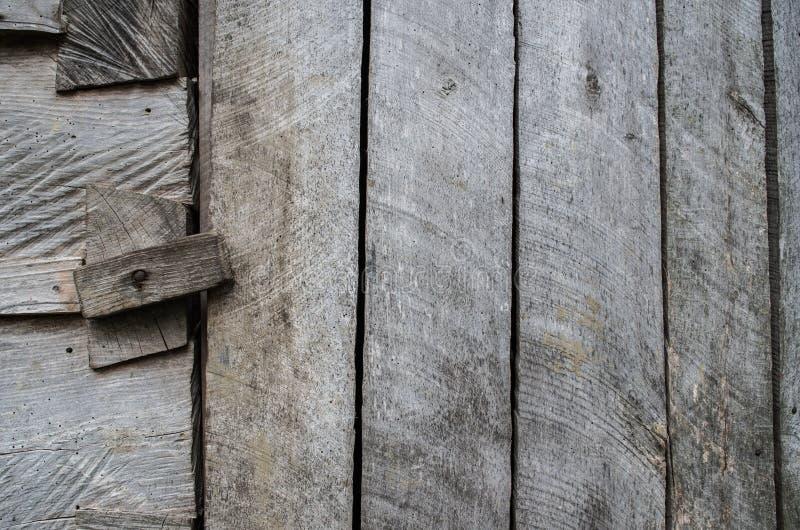 Mörkt - grå färger red ut den lantliga lantliga träladugårdväggen, dörren, porten, primirive bakgrund för textur för closeup för  fotografering för bildbyråer