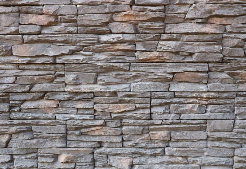 Mörkt - grå och brun cladding för yttre vägg som göras av ojämna naturliga stenar Stenpanel, royaltyfria foton