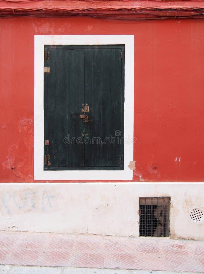 Mörkt - gröna trästängda slutare i ett vitt inramat fönster i en gammal bekymrad röd målad vägg royaltyfria bilder