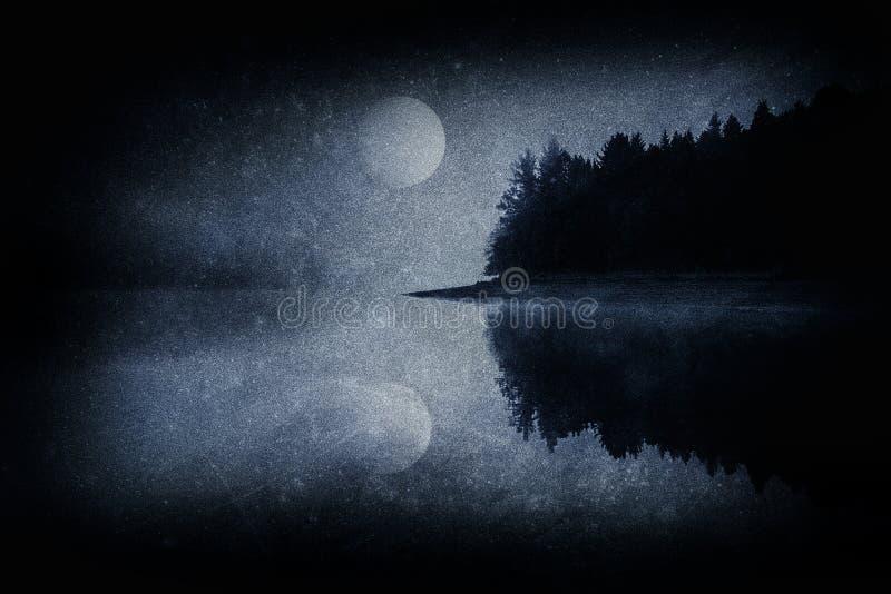 Mörkt läskigt landskap med en sjö en skog och en fullmåne royaltyfria bilder