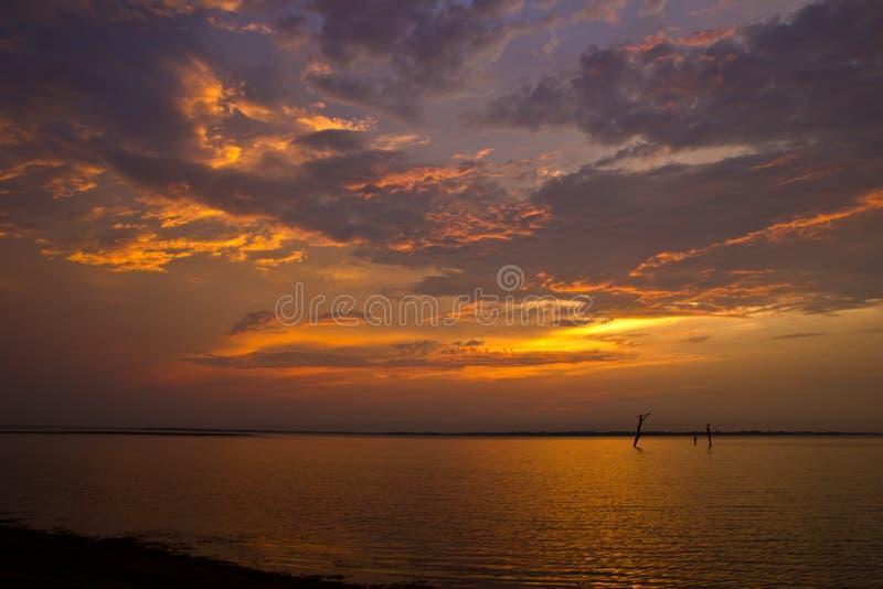 mörkt lynnigt för oklarheter över solnedgång för havsskystorm arkivbilder
