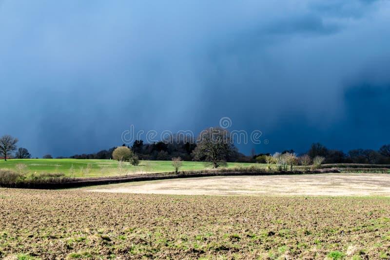 Mörkt moln, stormar och solsken med UK-väder som kan ändras i tidig vår fotografering för bildbyråer