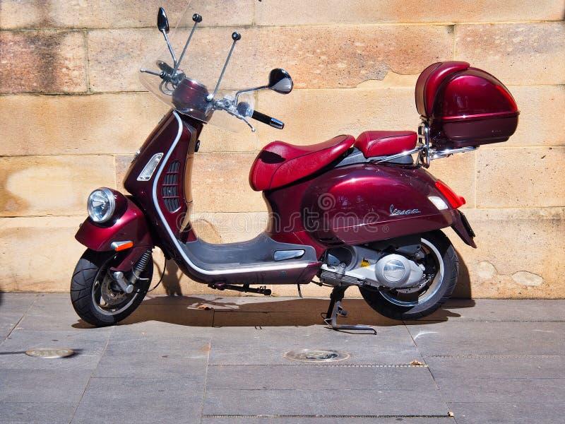Mörkt - röd Vespasparkcykel som parkeras nära den gamla sandstenväggen royaltyfria foton
