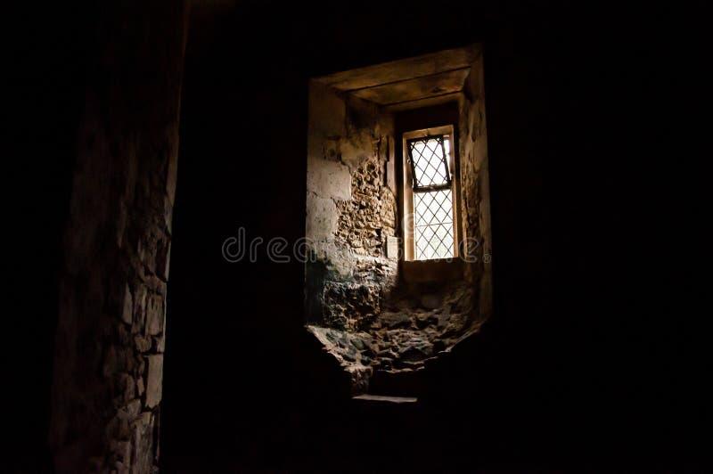 Mörkt rum med det detaljerade fönstret - Lacock royaltyfri bild