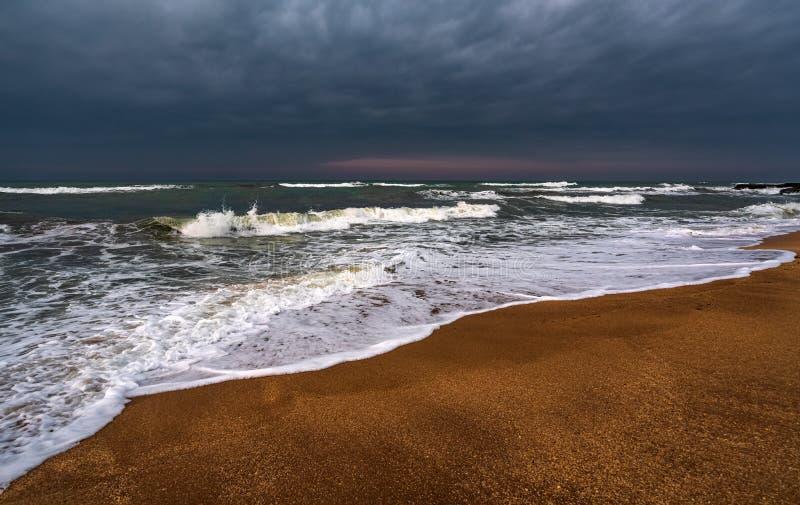 Mörkt stormigt hav och tom strand royaltyfri foto