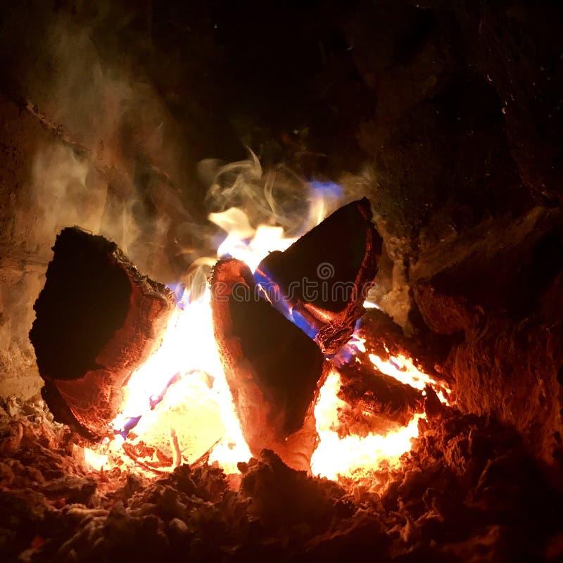 Mörkt svart kol för härligt flammabruntträ på ljus gul brand inom metallfyrpanna arkivfoton
