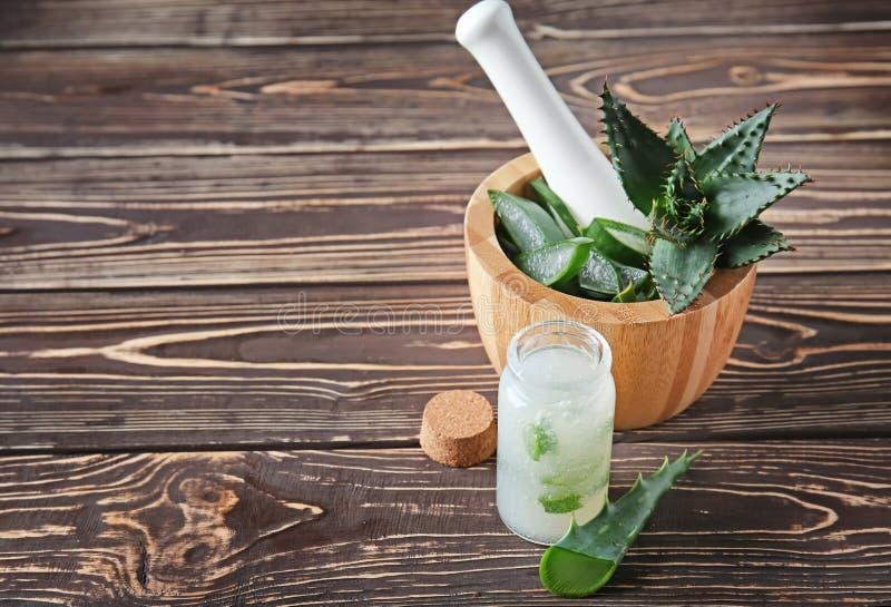 Mörser mit frischer Aloe Vera und Flasche Saft auf Holztisch stockbild