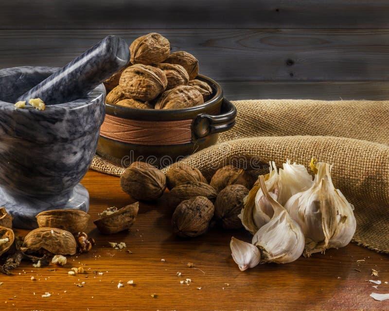 Mörser und Stampfe mit griechischem nuts Knoblauch der frischen Kräuter stockbild
