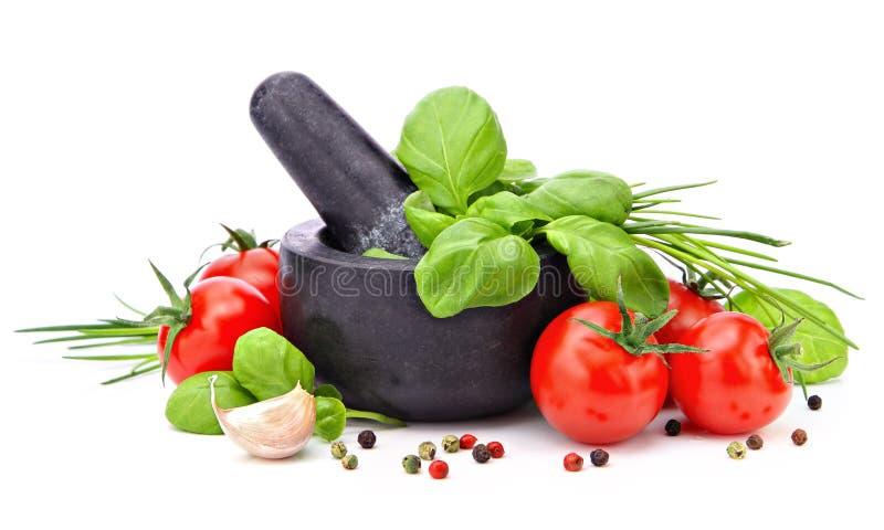 Mörtel mit Basilikum, Knoblauch, Tomaten und Pfeffer stockbilder