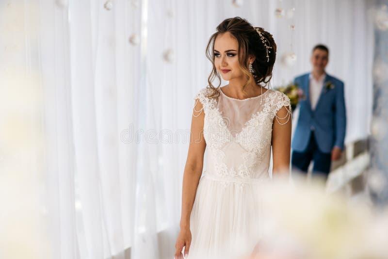 Möte av bruden och av brudgummen i det ljusa rummet Man bak kvinna med blommor i händer royaltyfria foton