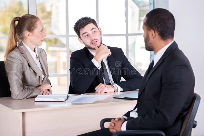 Möte av en klient Sitta för tre lyckat affärspersoner arkivfoto