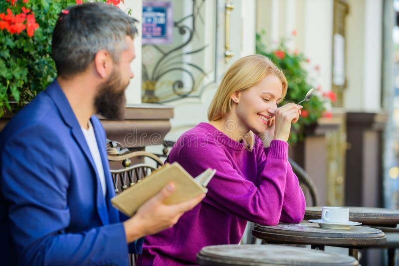 Möte av folk med liknande intressen Mannen och kvinnan sitter kaféterrassen Flickvän för fynd för gemensamt intresse för litterat royaltyfria foton