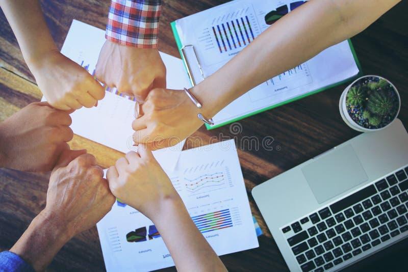 Möte av teamworkbegrepp, kamratskap, gruppfolk med bunten av händer som visar enhet efter lyckade förhandlingar på kontoret royaltyfri foto