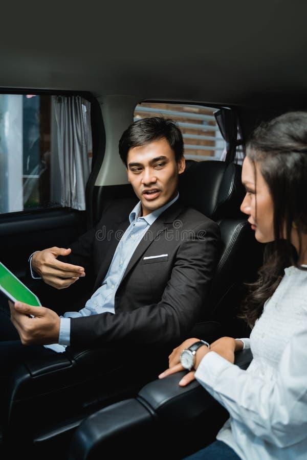 Möte för två affärspersoner, medan sitta på passagerareplats av bilen fotografering för bildbyråer