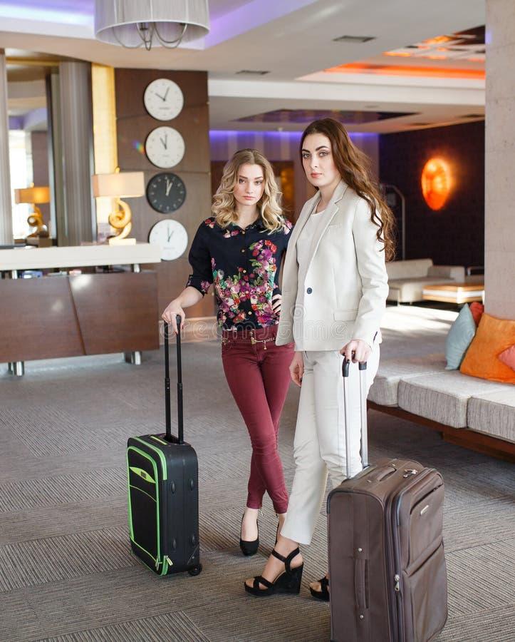 Möte på hotellmottagandet, flickor med resväskor i hotelllobbyen royaltyfria foton