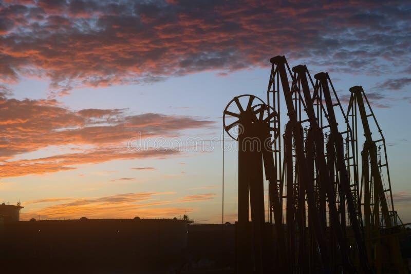 Múltiples del cargo de la silueta de la estación de petróleo en el puerto marítimo en la puesta del sol imagenes de archivo