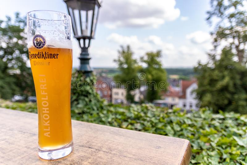 MÚN BENTHEIM, Baja Sajonia, Alemania - 18 de julio de 2019: Vidrio de cerveza alto que se sienta en una tabla imagen de archivo libre de regalías