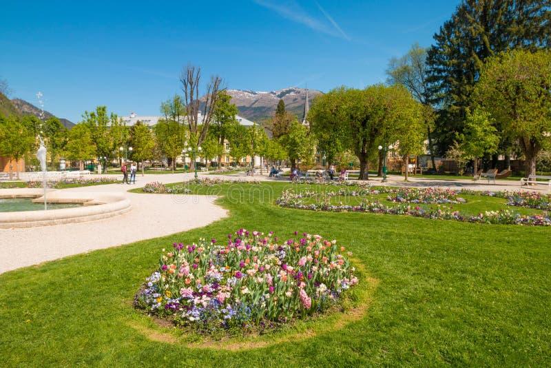 Mún Ischl, Austria - 20 de abril de 2018: Gente que se relaja en un parque hermoso de Kurpark con las camas de flor coloridas en  foto de archivo