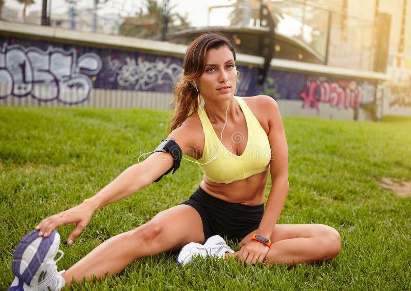 Músculo caucásico joven de la mujer que estira al aire libre foto de archivo libre de regalías