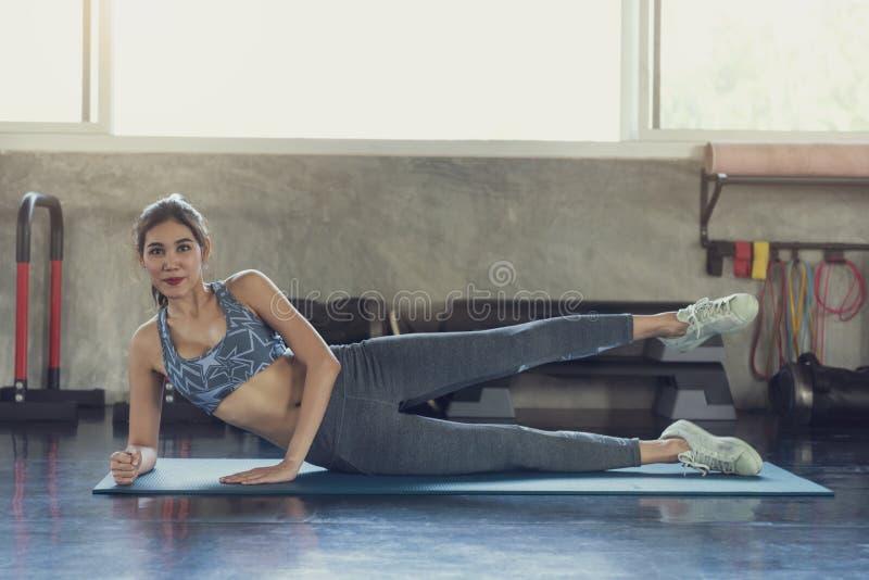 Músculo desportivo de sorriso asiático novo do estiramento da mulher após o exercício do gym na aptidão fotografia de stock