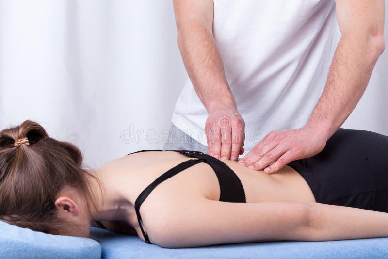 Músculo tocante do fisioterapeuta da parte traseira foto de stock