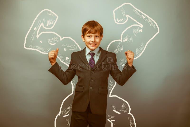 Músculos adolescentes del bíceps de las demostraciones del hombre de negocios del muchacho del fotos de archivo libres de regalías