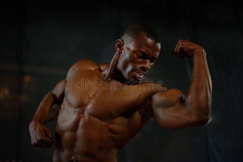 Músculos del primer del culturista hermoso afroamericano que presenta con el torso desnudo en el fondo negro del estudio fotografía de archivo libre de regalías