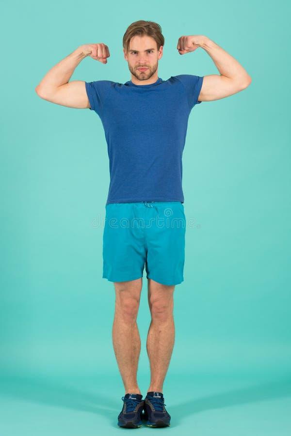 Músculos do cabo flexível do atleta com bíceps Desportista da forma no uniforme azul do esporte Homem farpado com cabelo à moda C imagens de stock royalty free