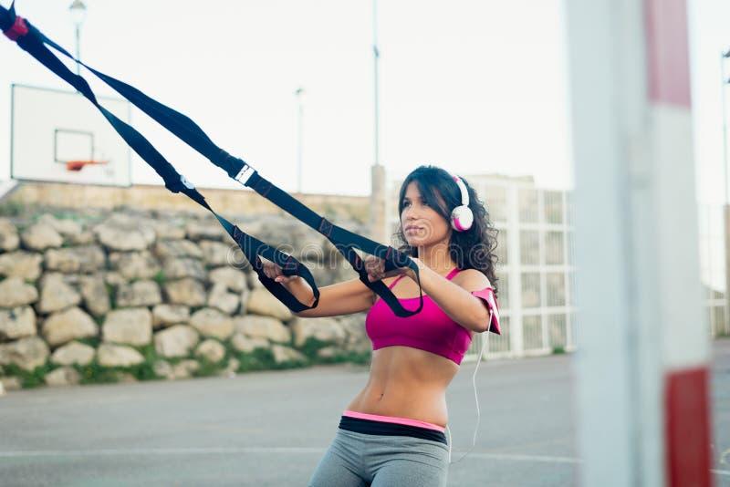 Músculos do treinamento da mulher com as correias da aptidão do trx fotos de stock