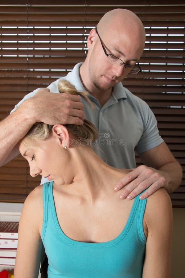 Músculos pacientes del cuello del stretchesfemale del quiropráctico foto de archivo