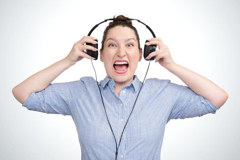 Música agressiva de escuta da moça emocional do retrato nos fones de ouvido foto de stock