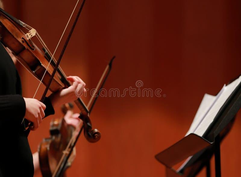 Música clássica Violinistas no concerto Amarrado, violinistCloseup do músico que joga o violino durante uma sinfonia imagens de stock royalty free