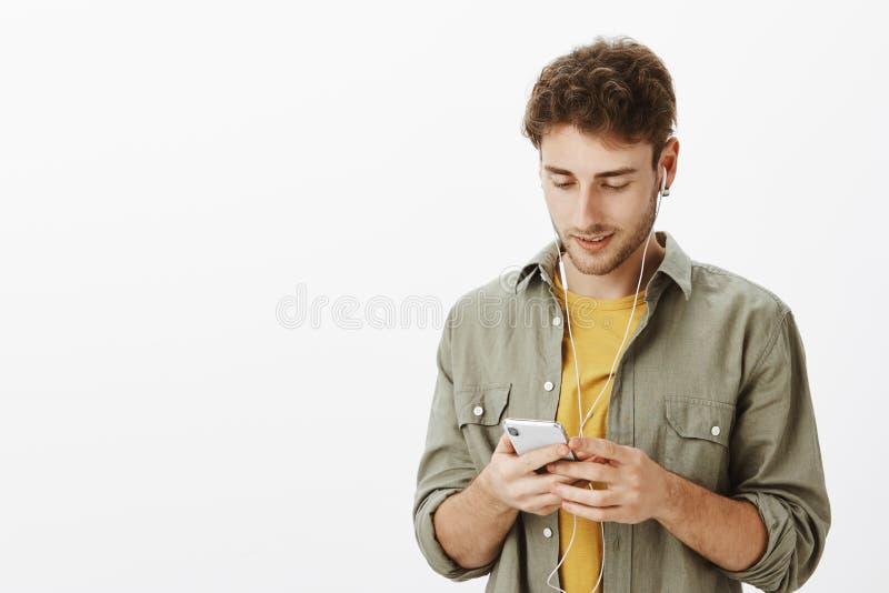 Música da colheita do dia no Internet Homem encaracolado-de cabelo despreocupado considerável com a barba, guardando o smartphone foto de stock royalty free