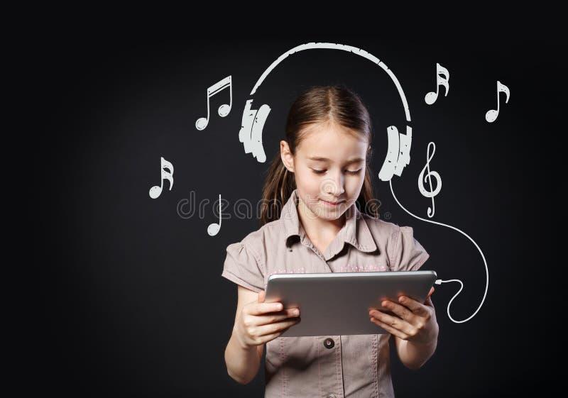 Música da criança e do Internet da tabuleta, fones de ouvido imaginários na menina imagens de stock